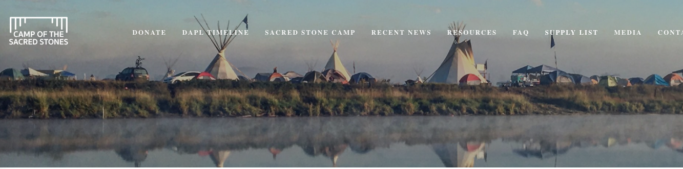 A line of tents and teepees along a river