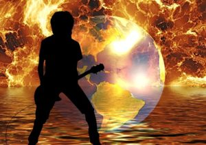 silhouette of guitarist in front of flaming earth